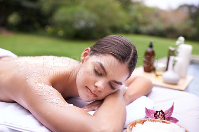 Buy stock photo Shot of a young woman enjoying a salt exfoliation treatment