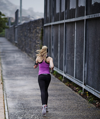 Buy stock photo Rearview shot of a young woman running along a path