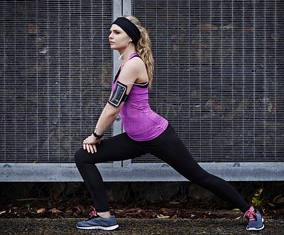 Buy stock photo Shot of a young woman stretching her legs before a run