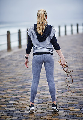 Buy stock photo Rearview shot of a young woman exercising outdoors with a skipping rope