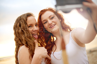 Buy stock photo Shot of two girlfriends taking selfies together outdoors