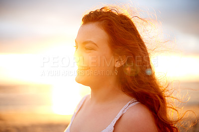 Buy stock photo Shot of a happy young woman spending time at the beach