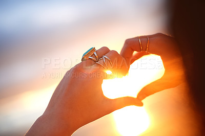 Buy stock photo Cropped shot of a woman making a heart shape with her hands against a sunset