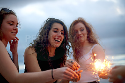 Buy stock photo Shot of girlfriends having fun with sparklers outdoors