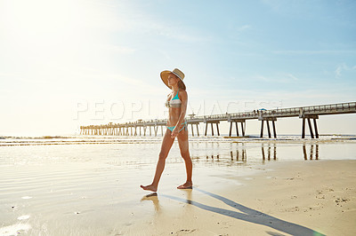Buy stock photo Shot of an attractive young woman walking on the beach