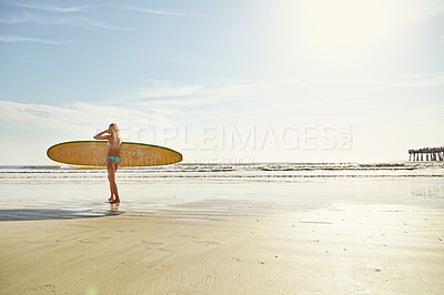 Buy stock photo Rearview shot of an attractive young woman carrying her surfboard on the beach
