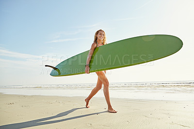 Buy stock photo Shot of an attractive young woman carrying her surfboard on the beach