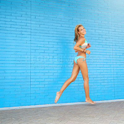 Buy stock photo Portrait of an attractive young woman running against a blue brick wall