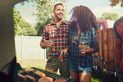 Buy stock photo Shot of a young couple standing by a barbecue grill outside