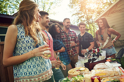 Buy stock photo Shot of a group of friends having lunch in their backyard