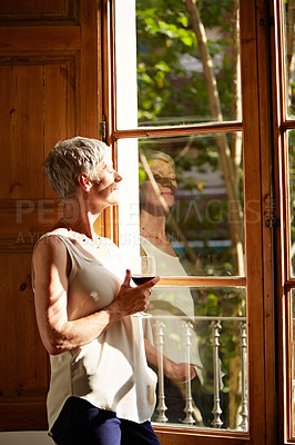 Buy stock photo Shot of a mature woman standing by a window drinking a glass of wine