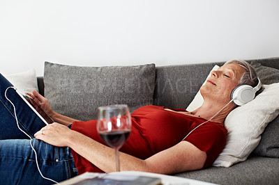 Buy stock photo Shot of a mature woman lying on her sofa listening to music on a digital tablet and drinking wine