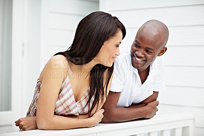 Buy stock photo Shot of a young couple leaning on the railing of their balcony
