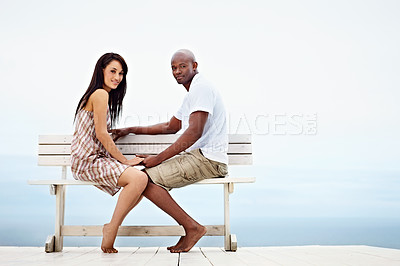 Buy stock photo Portrait of a young couple sitting on a bench on a boardwalk