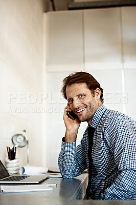 Buy stock photo Shot of a businessman sitting at his desk talking on a cellphone