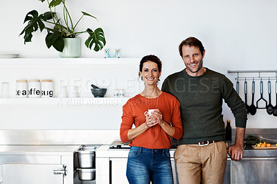 Buy stock photo Portrait of a smiling mature couple standing in their kitchen