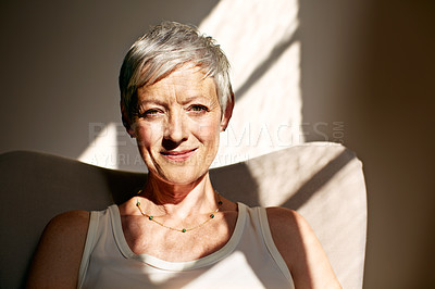 Buy stock photo Portrait of a mature woman sitting in a chair bathed in sunlight