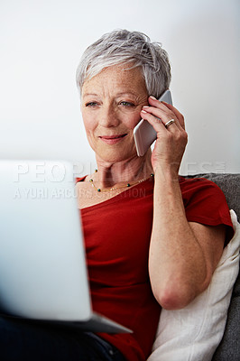 Buy stock photo Shot of a mature woman sitting in her living room using a laptop and talking on the phone