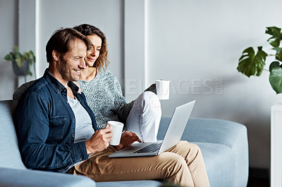 Buy stock photo Shot of a mature couple sitting on their sofa using a laptop