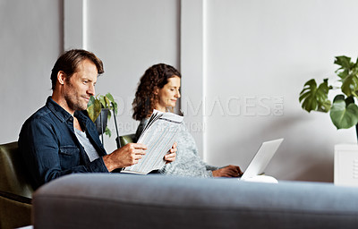Buy stock photo Shot of a content mature couple sitting in their living room reading the newspaper and using a laptop