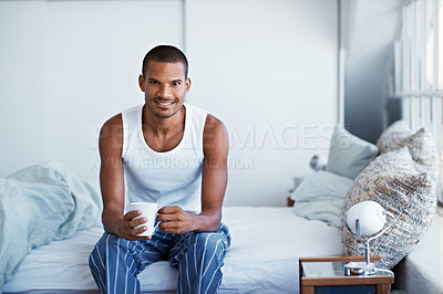 Buy stock photo Portrait of a young man sitting on his bed drinking coffee