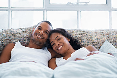 Buy stock photo Portrait of a smiling young couple lying in bed
