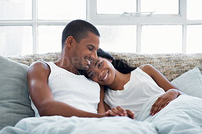 Buy stock photo Shot of a smiling young couple lying in bed