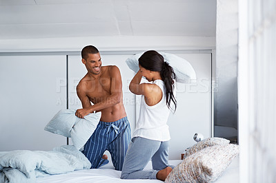Buy stock photo Shot of a young couple sitting on their bed having a pillow fight