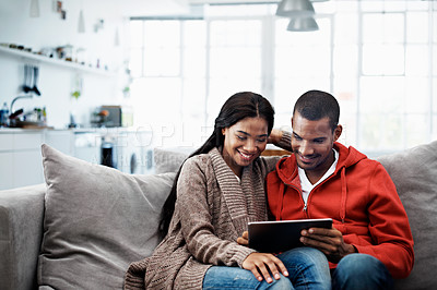 Buy stock photo Shot of a smiling young couple sitting on their sofa using a digital laptop