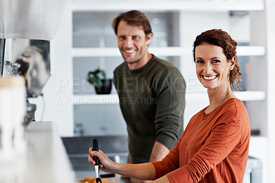 Buy stock photo Portrait of a smiling mature couple cooking together in their kitchen
