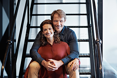 Buy stock photo Portrait of a smiling mature couple sitting on stairs in their loft