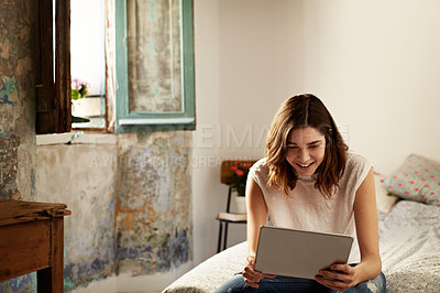 Buy stock photo Shot of a young woman sitting on her bed using a digital tablet