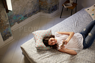 Buy stock photo High angle shot of a young woman lying on her bed using a cellphone
