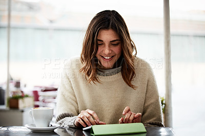 Buy stock photo Shot of a young woman sitting in a cafe using a digital tablet
