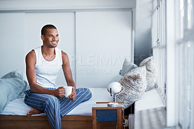 Buy stock photo Shot of a young man sitting on his bed drinking coffee