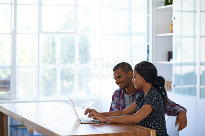 Buy stock photo Shot of a young couple sitting at their dining table using a latpop