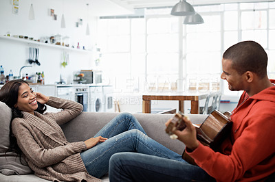 Buy stock photo Shot of a young man sitting on the living room sofa serenading his wife with a guitar