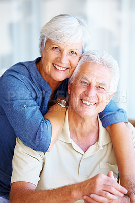 Buy stock photo Portrait of happy senior couple sitting together a home and smiling