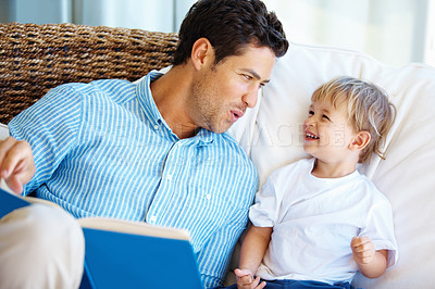 Buy stock photo Father and son reading a story book and smiling