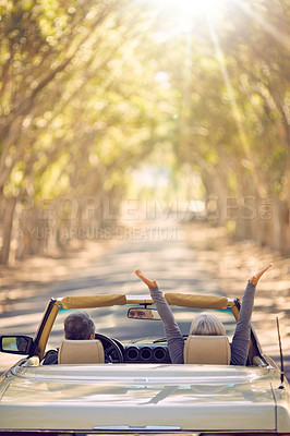 Buy stock photo Shot of a senior woman raising her hands in the air while on a roadtrip with her husband