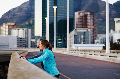 Buy stock photo Shot of a young couple stretching before their run in the city