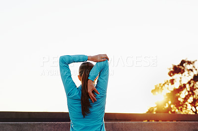 Buy stock photo Rearview shot of a woman stretching before her run