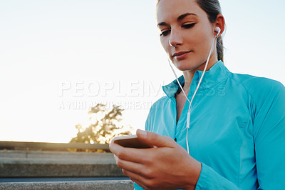 Buy stock photo Shot of a young woman listening to music while out running