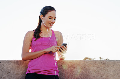 Buy stock photo Shot of an athletic young woman choosing a song before her run in the city