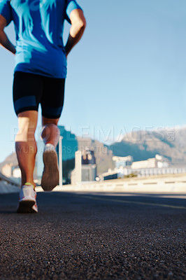Buy stock photo Rearview shot of an athletic man running in the city