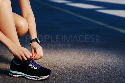 Buy stock photo Cropped shot of an athletic woman tying her laces before starting her run