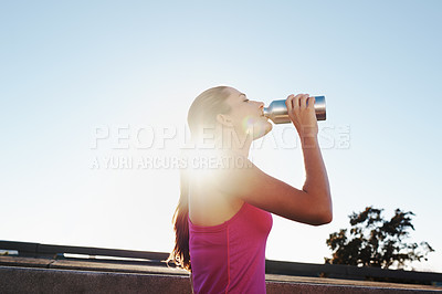 Buy stock photo Cropped shot of an athletic young woman taking a water break while running in the city