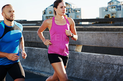 Buy stock photo Cropped shot of an athletic couple running in the city
