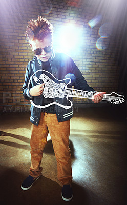 Buy stock photo Shot of a boy playing music on an imaginary guitar