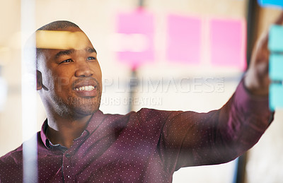 Buy stock photo Shot of a male designer looking at sticky notes on a glass wall